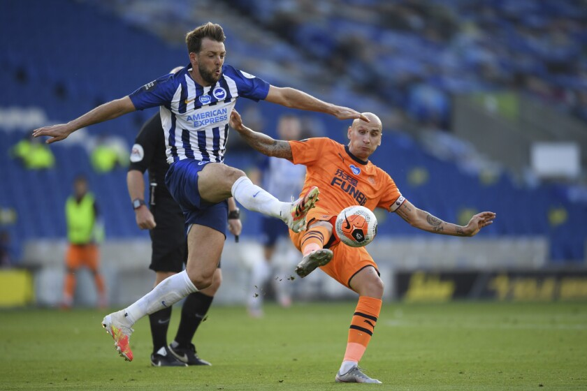 Brighton's Dale Stephens, left, fights for the ball with Newcastle's Jonjo Shelvey during the English Premier League soccer match between Brighton and Newcastle United at the American Express Community Stadium in Brighton, England, Monday, July 20, 2020. (Mike Hewitt/Pool via AP)