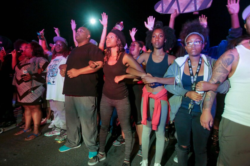 Protesters lock arms in front of a police line in El Cajon after the police shooting of Alfred Olango.