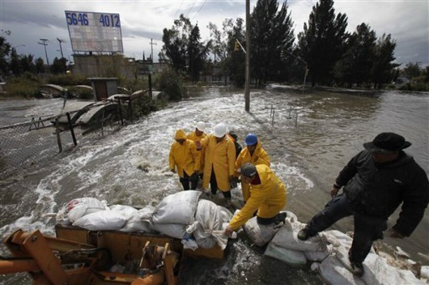 Workers place sand bags to prevent more flooding after heavy rains in Nezahualcoyotl, a town adjacent to Mexico City,Thursday, Feb. 4, 2010. (AP Photos/Eduardo Verdugo)