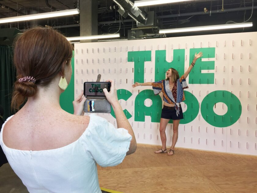 Mary Carr, left, takes a picture of visitor Melana Preston of Encinitas at The Cado, a pop-up educational installation about avocados now on display through Sept. 22 in San Marcos. Carr created the exhibit with her sister, Anne Buehner.