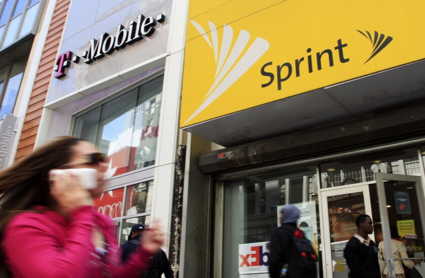 In this April 27, 2010, photo, a woman using a cellphone walks past T-Mobile and Sprint stores in New York.