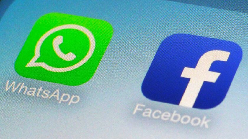 WhatsApp and Facebook app icons on a smartphone.