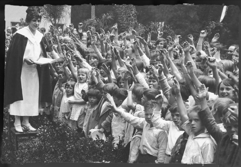 Evangelist Aimee Semple McPherson addressing a throng of children in front of her home adjoining Angelus Temple, 1926.