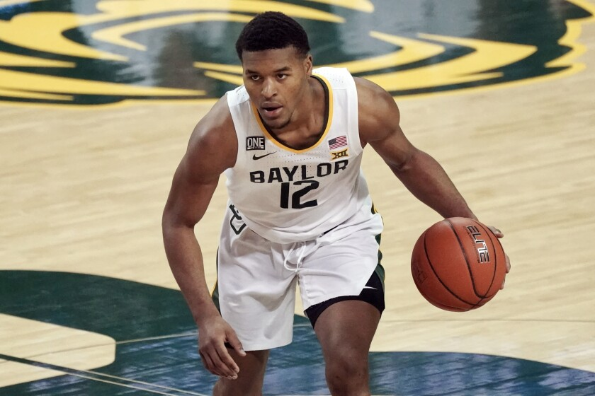 FILE - Baylor's Jared Butler (12) brings the ball up the court against Auburn during the second half of an NCAA college basketball game in Waco, Texas, in this Saturday, Jan. 30, 2021, file photo. Butler has made The Associated Press All-America first team, announced Tuesday, March 16, 2021.(AP Photo/Chuck Burton, File)