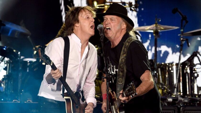 Paul McCartney and Neil Young share a microphone at the 2016 Desert Trip festival in Indio.