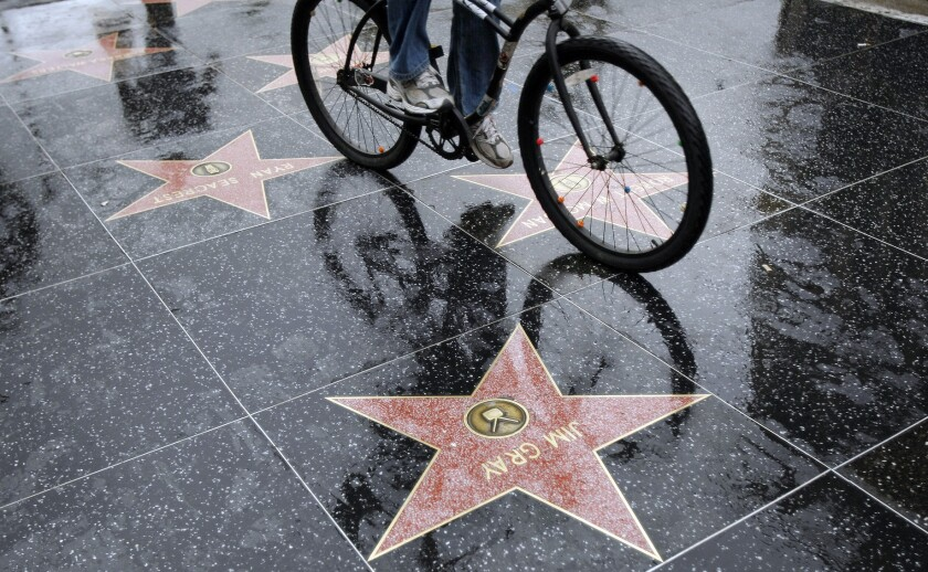 A cyclist makes his way on a wet Hollywood Boulevard.