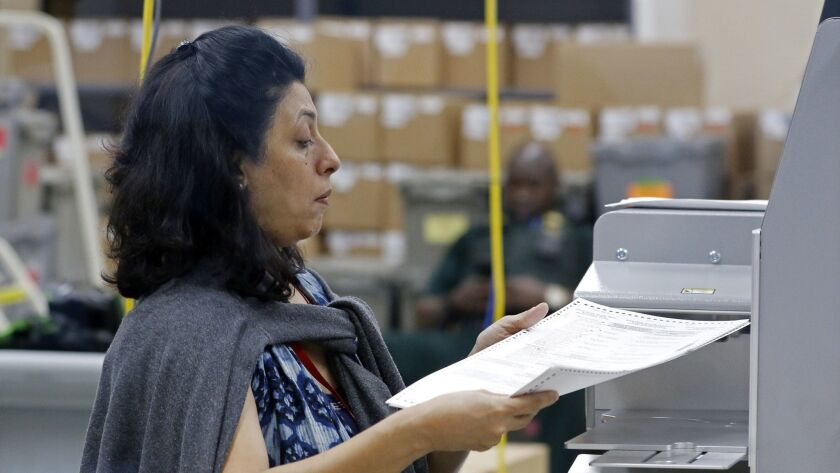 An election worker feeds ballots into a tabulation machine at the Broward County Supervisor of Elections office on Saturday.