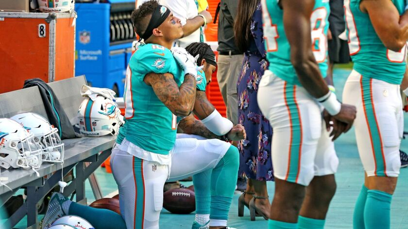 Miami Dolphins receivers Kenny Stills and Albert Wilson kneel during the national anthem before a game against the Tampa Bay Buccaneers on Aug. 9.