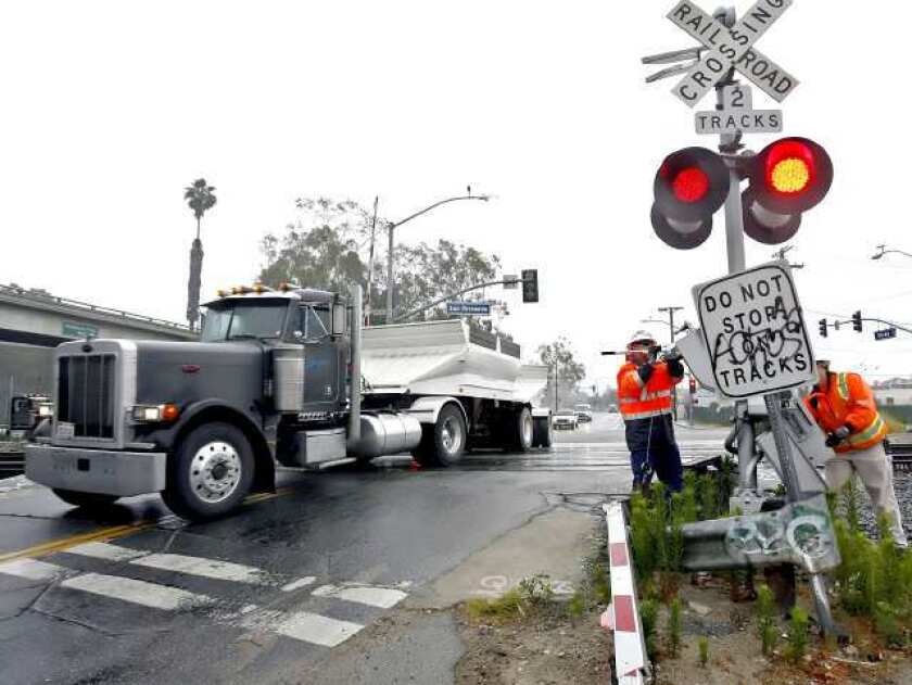Metrolink workers repair a broken railroad crossing arm at the tracks on Doran St. and San Fernando Road in Glendale on Friday, June 17, 2011. The arm was broken after 6 a.m.