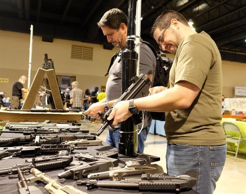 Un hombre prueba un arma durante la Feria de Armas de Miami en Miami, Florida (Estados Unidos). EFE/Archivo