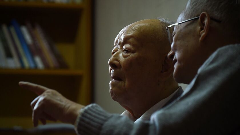 Zhou Youguang, left, talks with his son Zhou Xiaoping at his home in Beijing in 2015.