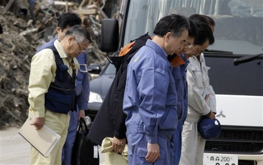 Japan's Prime Minister Naoto Kan, center at right, bows with other officials for the victims of the March 11 earthquake and tsunami-destroyed town of Rikuzentakata, Iwate Prefecture, northern Japan, Saturday, April 2, 2011. (AP Photo/Lee Jin-man)