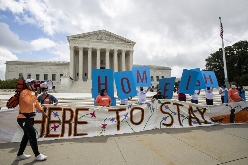 Deferred Action for Childhood Arrivals (DACA) recipient Roberto Martinez, left, celebrates with other DACA recipients in front of the Supreme Court on Thursday, June 18, 2020, in Washington. The Supreme Court on Thursday rejected President Donald Trump's effort to end legal protections for 650,000 young immigrants, a stunning rebuke to the president in the midst of his reelection campaign. (AP Photo/Manuel Balce Ceneta)