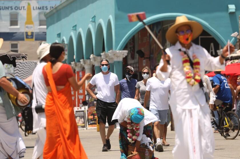 People walk along the Venice boardwalk