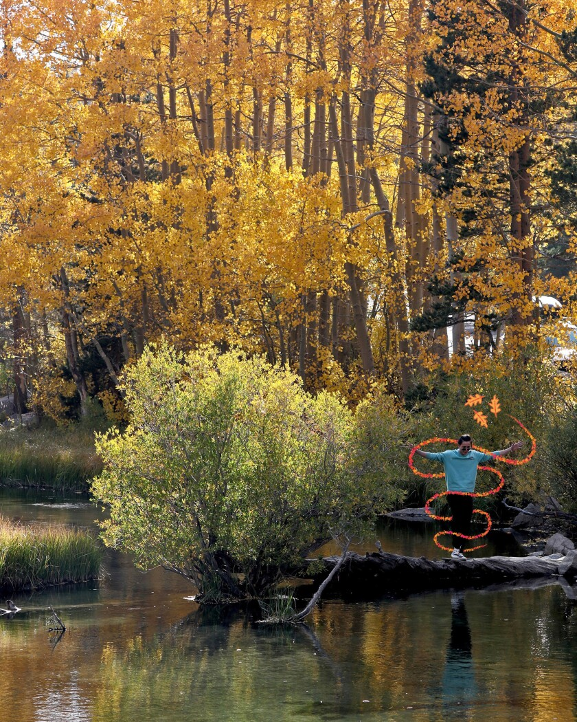 Visitors to the Lake Sabrina area in the Inyo National Forest pose for photos with colorful fall foliage.