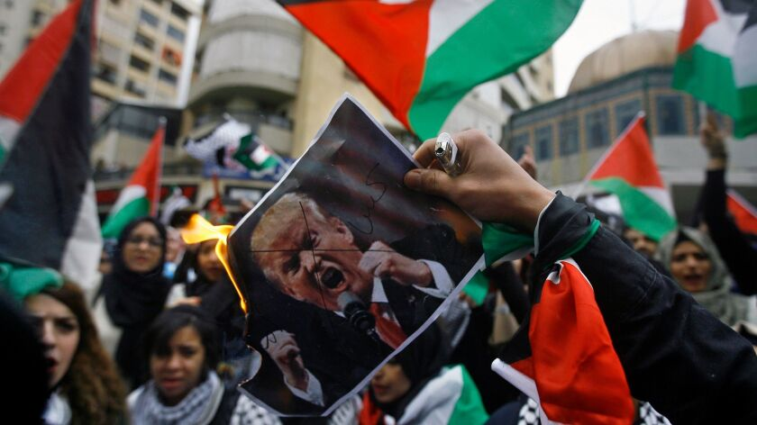 Lebanese and Palestinians students, burn a poster of U.S. President Donald Trump as they take part i