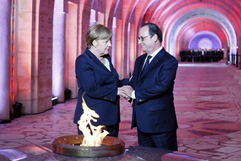 French President Francois Hollande, right, and German Chancellor Angela Merkel pay their respect in front of the Eternal Flame at the Douaumont's Ossuary, in Douaumont, northeastern France, Sunday May 29, 2016, during a remembrance ceremony to mark the centenary of the battle of Verdun. Hollande an
