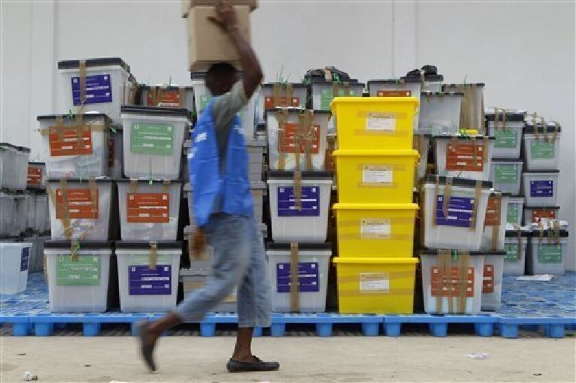A poll worker walks past ballot boxes as he helps organize election materials being brought in from polling stations, at a National Election Commission warehouse in Monrovia, Liberia Wednesday, Oct. 12, 2011. International and local election observers said Liberia's presidential election Tuesday was peaceful and there were no reported serious breaches in voting.(AP Photo/Rebecca Blackwell)