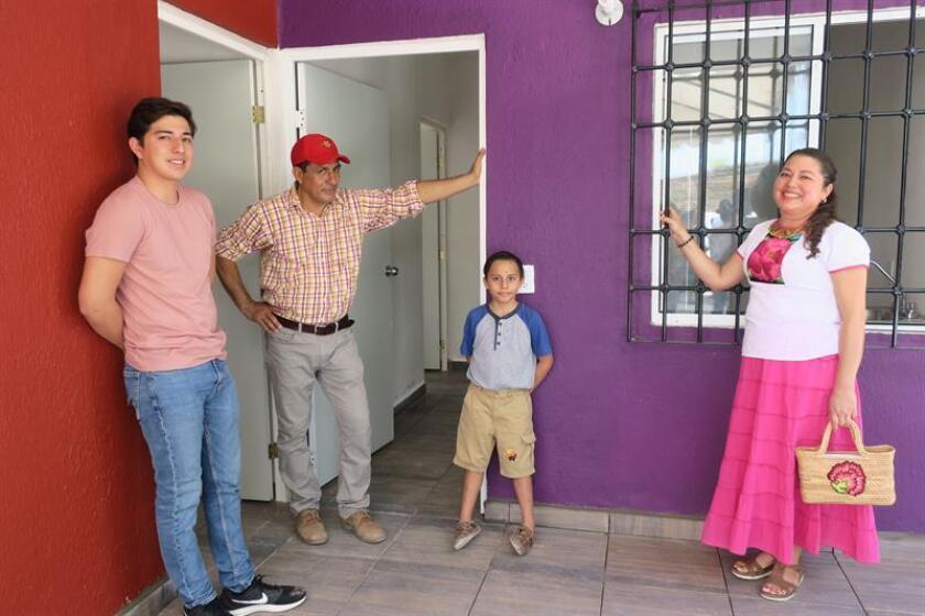 La familia Ruiz posa a las afueras de su nueva casa hoy, miércoles 15 de agosto de 2018, en Ciudad Hidalgo, en el estado de Oaxaca (México). EFE