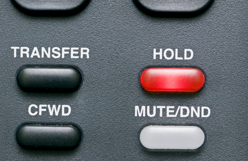 Macro shot of a telephone's feature buttons with the hold button red and activated.