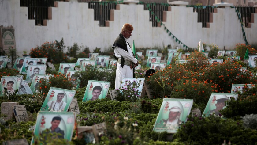 A man offers prayers Monday in Sanaa, Yeman, at the portrait-adorned grave of a relative killed in the ongoing conflict.