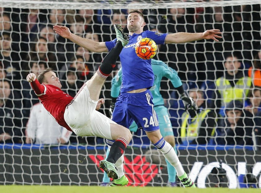 Manchester United's captain Wayne Rooney gets in a shot despite the challenge of Chelsea's Gary Cahill during the English Premier League soccer match between Chelsea and Manchester United at Stamford Bridge stadium in London, Sunday, Feb. 7, 2016.  (AP Photo/Frank Augstein)