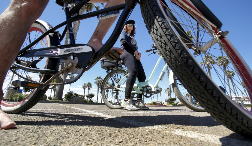 More bike lanes would come to San Diego's urban neighborhoods under a new city proposal. Craig Lester and Kimberly Paige from Pacific Beach, above, rode on the Mission Beach boardwalk in March.