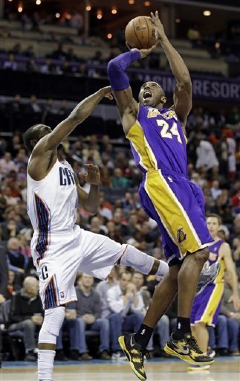 Los Angeles Lakers' Kobe Bryant, right, shoots over Charlotte Bobcats' Kemba Walker, left, during the second half of an NBA basketball game in Charlotte, N.C., Friday, Feb. 8, 2013. The Lakers won 100-93. (AP Photo/Chuck Burton)