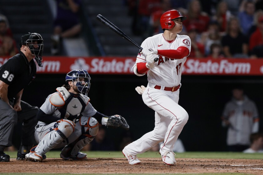 Los Angeles Angels' Shohei Ohtani watches his two-run home run next to Detroit Tigers catcher Eric Haase, center, and umpire Ryan Blakney during the fifth inning of a baseball game in Anaheim, Calif., Friday, June 18, 2021. (AP Photo/Alex Gallardo)