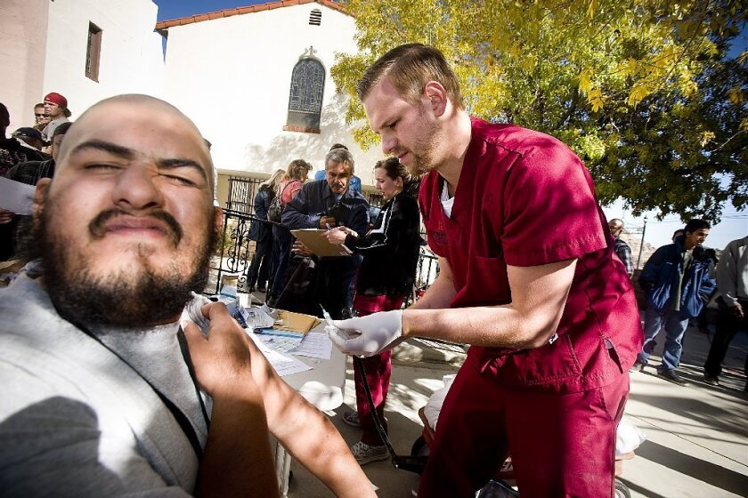 Ryan Hernandez grimaces while getting a flu shot in Victorville, Calif., in November. A new study says the vaccine reduced the risk of serious illness by 23%.