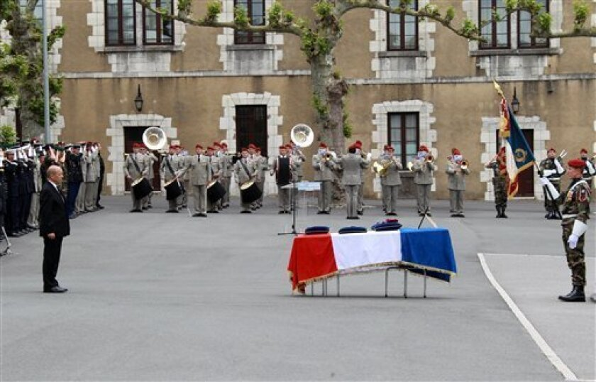 French Defense Minister Jean Yves Le Drian, left, stands before the coffin of Stephane Duval, a French soldier killed in Mali on April 29, 2013, during his military funeral in Bayonne, southwestern France, Tuesday, May 7, 2013. Duval is the sixth French soldier killed since the beginning of the military intervention in Mali. (AP Photo/Bob Edme)
