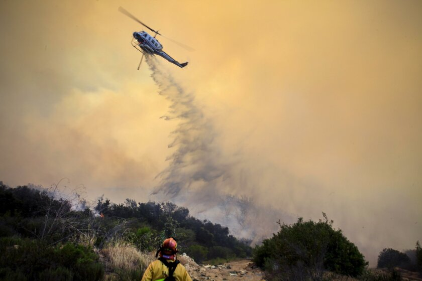 A San Diego County Sheriffs Department ASTREA helicopter makes a water drop on the Cocos Fire in San Marcos.