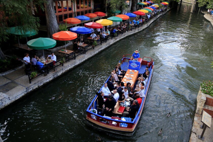 One of the Rio Taxi dinner/cocktail cruise charters floats past the colorful umbrellas at Casa Rio Restaurant on the San Antonio River along the river walk in San Antonio.