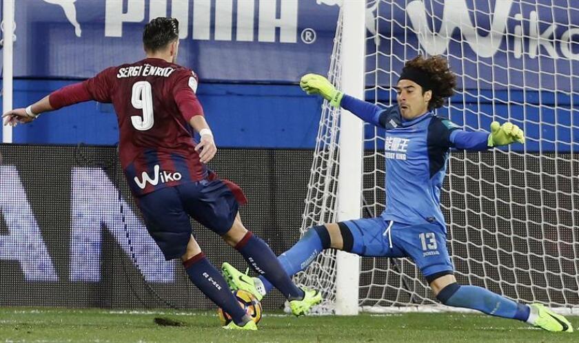 El delantero del Eibar Sergi Enrich (i) lanza para marcar gol ante el portero del Granada, Guillermo Ochoa durante el partido de la vigésima segunda jornada de Liga que disputan en el estadio de Ipurúa. EFE