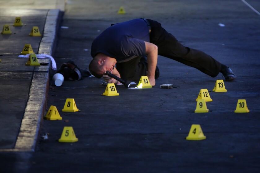San Bernardino police examine the scene of a fatal shooting in a parking lot.