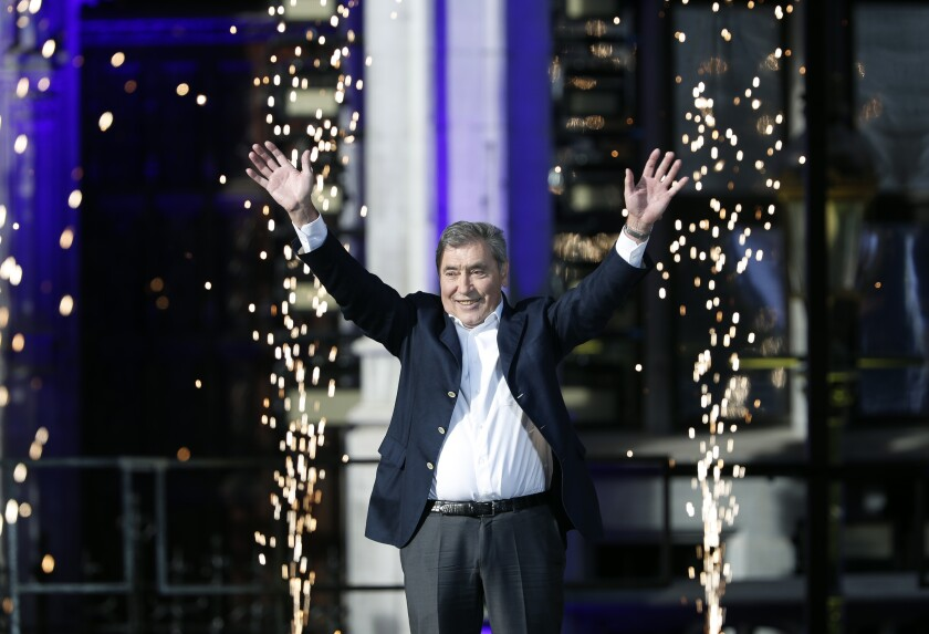 FILE - In this Thursday, July 4, 2019 file photo, former Belgian cycling champion Eddy Merckx waves during the Tour de France cycling race teams presentation at the Grand Place in Brussels, ahead of upcoming Saturday's start of the race. Belgian daily Het Nieuwsblad says cycling great Eddy Merckx has sustained head injuries in a crash while riding with friends. The newspaper says the 74-year-old Merckx crashed Sunday Oct. 13, 2019, and was admitted to a hospital in Dendermonde. Merckx is regarded by many as the greatest-ever cyclist who won five Tour de France titles and a record 34 stages. (AP Photo/Thibault Camus, File)