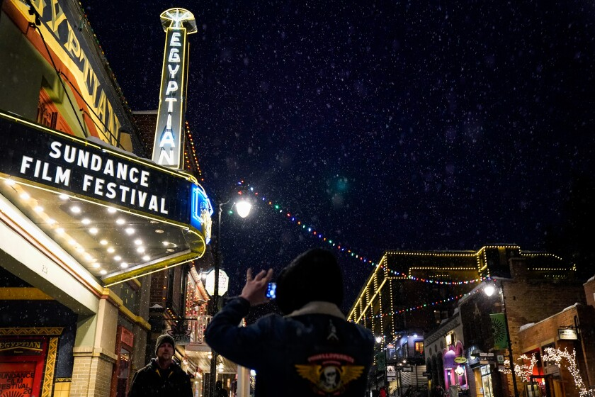 """People stand outside the Egyptian Theater with the marquee reading """"Sundance Film Festival."""""""