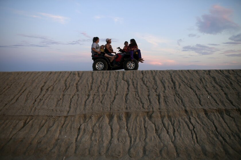 In this June 30, 2015 photo, the Rangel family takes a ride on their ATV along an embankment along one side of the community of Okieville, on the outskirts of Tulare, Calif. As California endures a fourth year of drought, water scarcity has become the new normal, inconveniencing millions of people