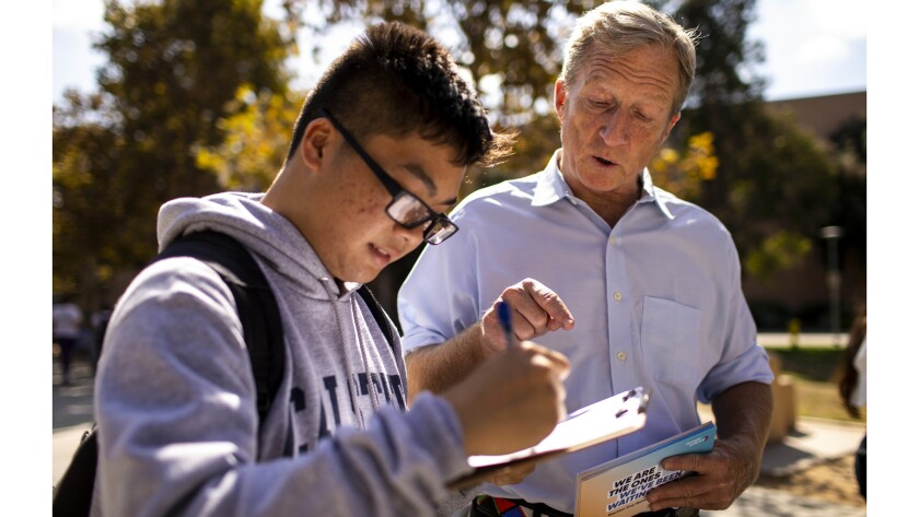 FULLERTON, CALIF. - OCTOBER 10: Tom Steyer helps Kevin Huy Nguyen, 18, fill out paperwork to registe