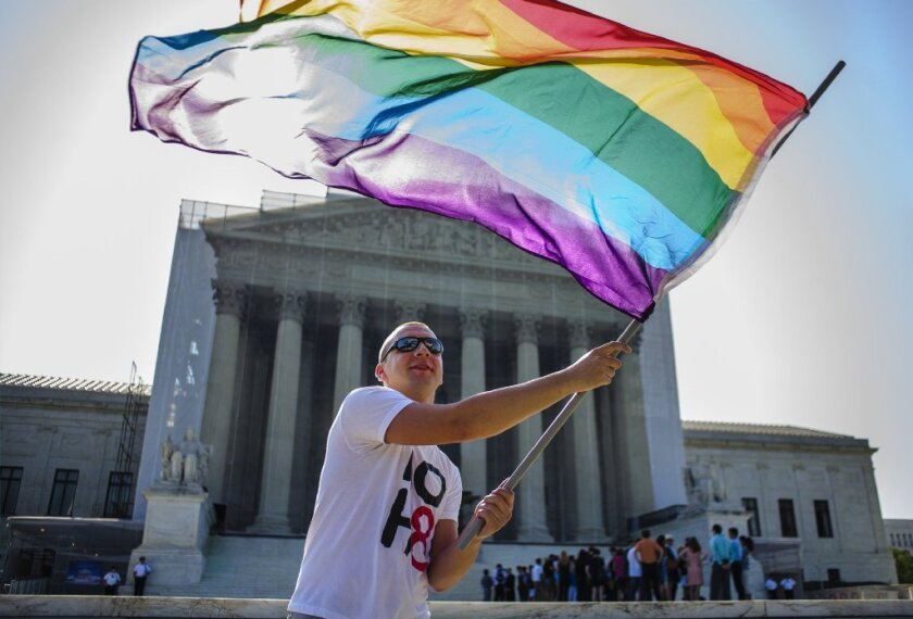 A demonstrator waves a pride flag in front of the U.S. Supreme Court.
