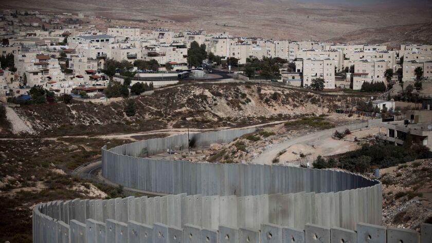 The east Jerusalem neighborhood of Pisgat Zeev is seen behind a section of Israel's separation barri