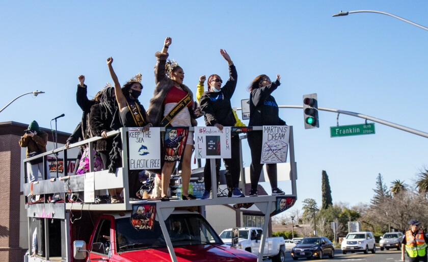 Participants cheer while riding atop a flatbed truck during a car caravan honoring Martin Luther King in Sacramento.
