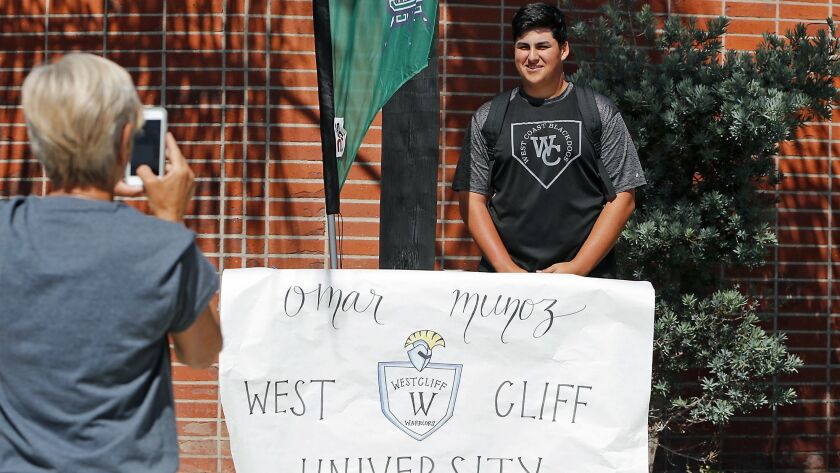 Baseball player Omar Munoz poses in front of his banner as he participates in a National Signing Day