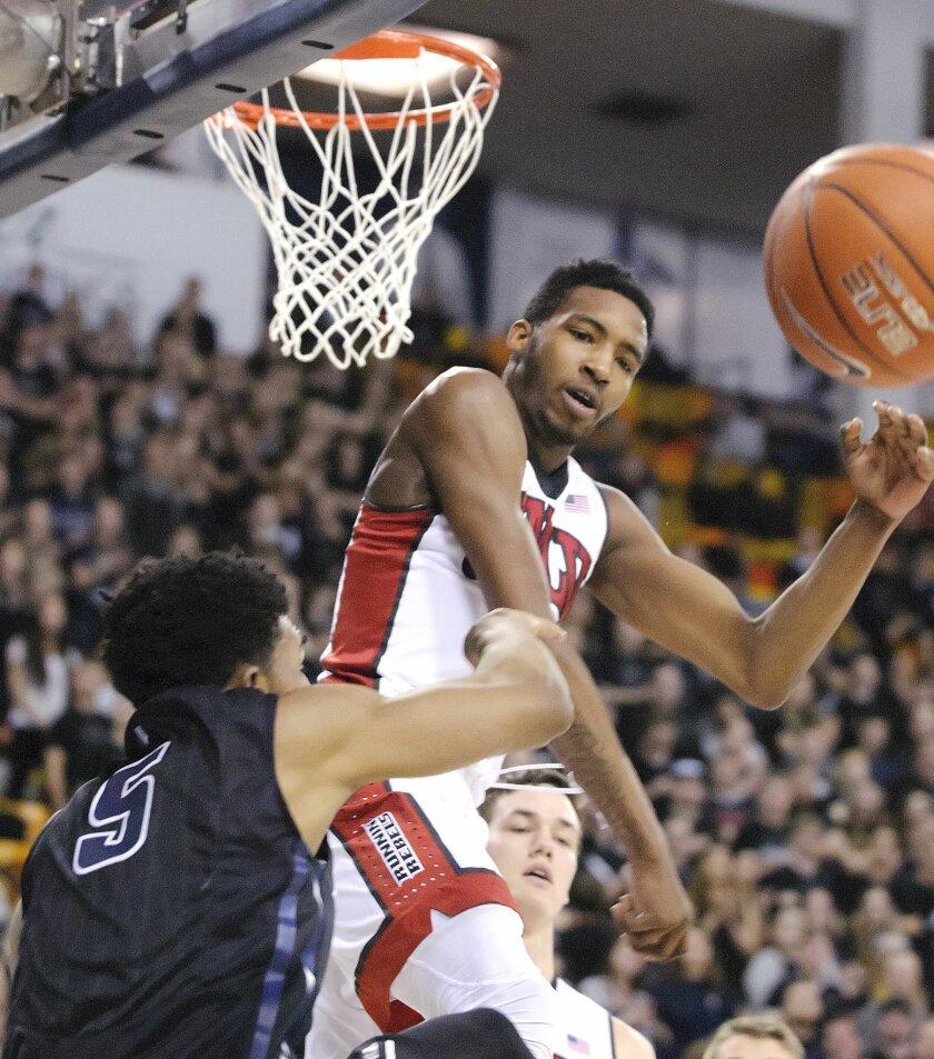 UNLV forward Derrick Jones Jr. (1) blocks the shot of Utah State guard Julion Pearre (5) during an NCAA college basketball game, Tuesday, Jan. 19, 2016, in Logan, Utah. (Eli Lucero/Herald Journal via AP) MANDATORY CREDIT