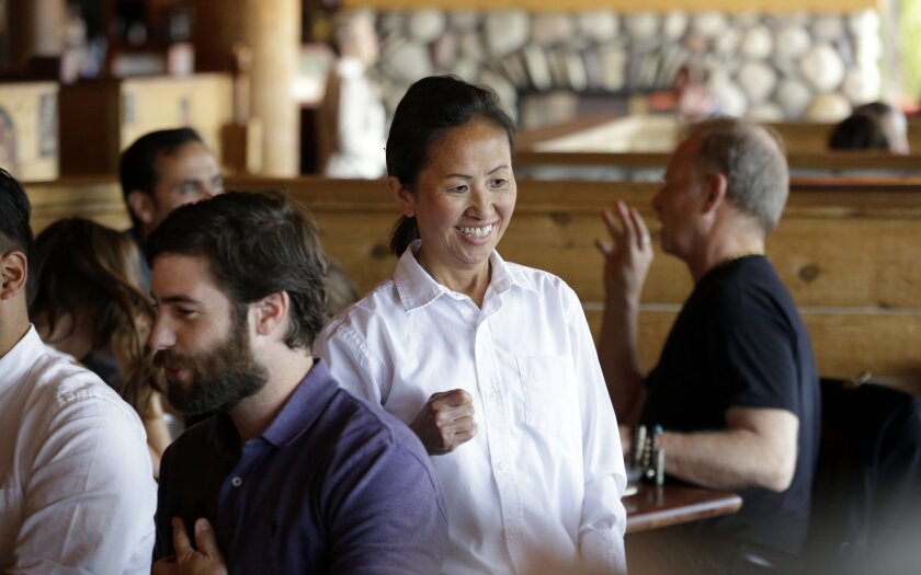 In this photo taken Monday, July 27, 2015, server Ling Powers smiles as she talks with customers at an Ivar's restaurant in Seattle. After Seattle's new minimum wage law took effect last April 1, Ivar's Seafood Restaurants announced that it was jacking up its prices by about 21 percent, eliminating tipping as a routine procedure, and immediately paying all its hourly workers a $15 per hour. They began the new pay rate three years earlier than the law required. (AP Photo/Elaine Thompson)