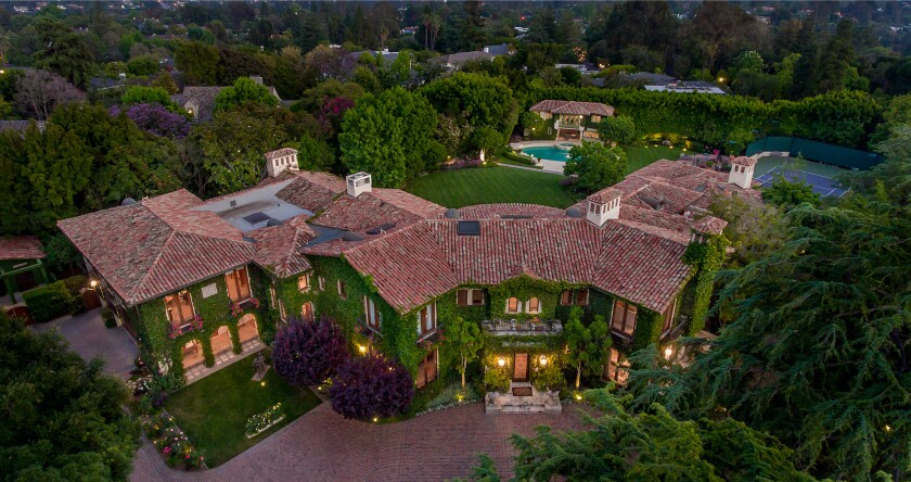 Across two park-like acres, the estate holds a 16,700-square-foot, ivy-draped villa, a two-story guesthouse, a swimming pool, a tennis court and aputting green.
