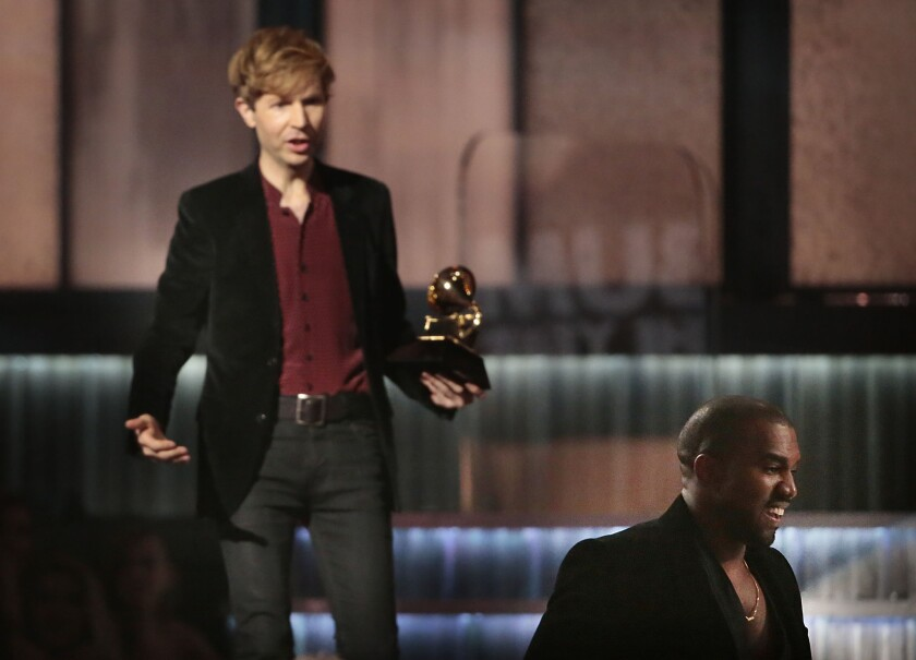 Kanye West , right, avoids contact with an inviting Beck after Beck won album of the year at the 57th Grammy Awards in Los Angeles on Feb. 8, 2015.