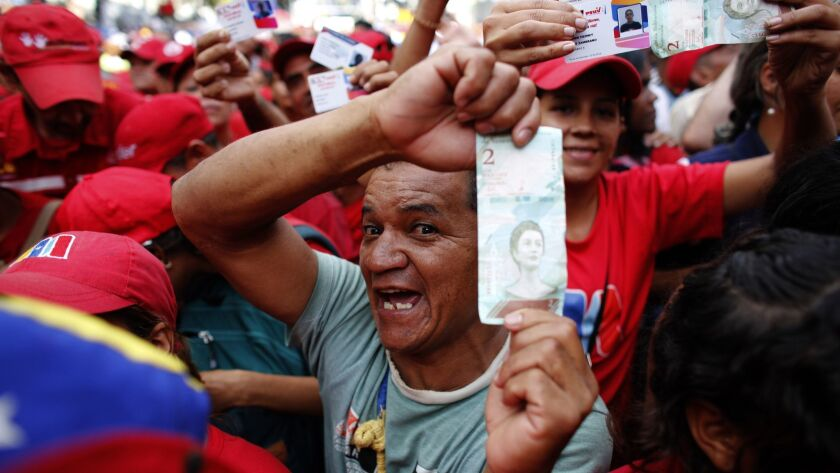 Pro-government supporters cheer as some hold up new bank notes and patriot identification cards during a rally in Caracas, Venezuela's capital, on Aug. 21, 2018. Others predicted more hardship ahead.