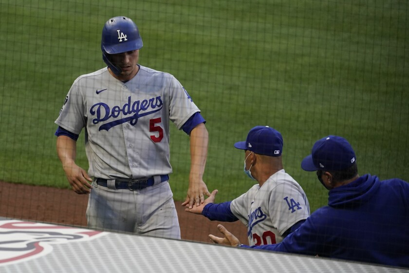 The Dodgers' Corey Seager gets a high-five from manager Dave Roberts after scoring in the fourth inning May 8, 2021.