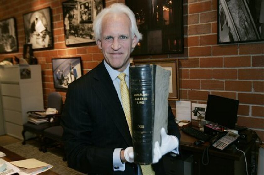 """In this photo taken in Dallas on Dec. 2, 2009, Robert Edsel, founder of the Monuments Men Foundation for the Preservation of Art, holds a lost  album that once belonged to Adolf Hitler, part of a series compiled for Hitler featuring photographs of art he wanted for his """"Fuehrermuseum,"""" a planned mu"""